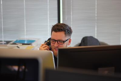 (Photo by Berkeley Communications on Unsplash). An image of an employee on a phone. The call center industry has traditionally high turnover rates, but for Dialamerica, offering an on demand payment benefit like DailyPay has helped improve retention.