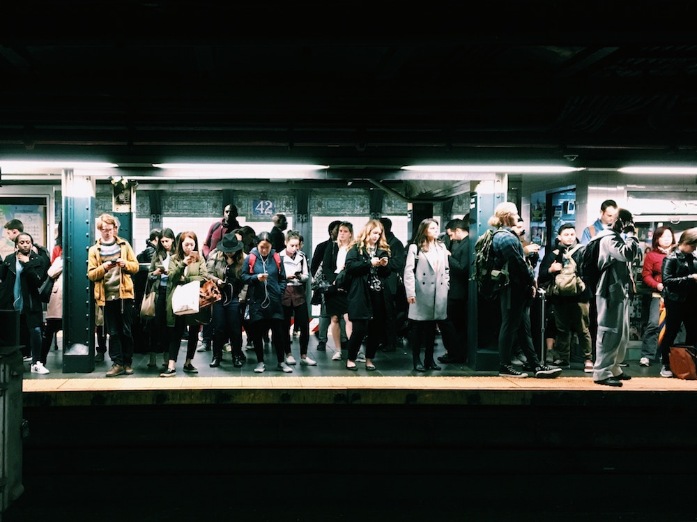 An image of working commuters waiting for the New York City Subway. A strong labor market has made it challenging for employers to retain employees and reduce employee attrition.