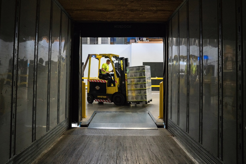 An image of a forklift unloading a truck at a warehouse. The holiday season forces many employers to increase their workforce to handle heightened demand.